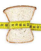 Pedazo de pan agarrado por cinta métrica — Foto de Stock