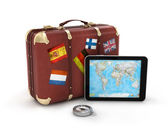 Vintage travel suitcase and touch pad — Stock Photo