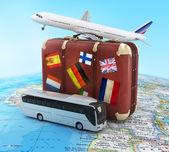 Plane, bus and suitcase on worldmap — Stock Photo