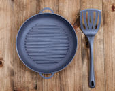 Frying pan and kitchen utensils on wooden table — Stock Photo