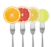 Citrus fruit on forks lime, orange, grapefruit, lemon — Stock Photo