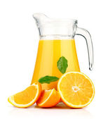 Orange juice in pitcher and oranges. — Stock Photo