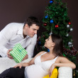 Happy pregnant couple near the christmas tree — Stock Photo