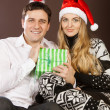 Happy couple in Christmas hats - Stock Photo