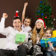 Happy family near the Christmas tree - Stock Photo