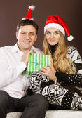 Happy couple in Christmas hats — Stock Photo