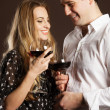 Young happy couple enjoying a glasses of wine - Stok fotoğraf