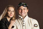 Young couple in retro style clothes over broun background — Stock Photo