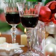 Glasses of red wine and Christmas decorations - Stock Photo
