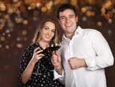 Portrait of a happy young couple on blurred lights background — Stock Photo