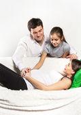 Giovane incinta famiglia rilassante sul divano — Foto Stock