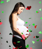 Happy pregnant woman touching her belly — Stock Photo