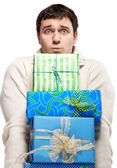 Surprised young man with presents — Stock Photo