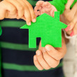 Family of four holding green house in hands — Stock Photo
