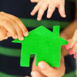 Stock Photo: Family of four holding green house in hands