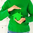 Little girl holding green house in hands — Stock Photo