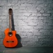 Acoustic guitar leaning on grungy wall — Stock Photo