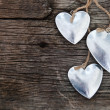 Metal hearts on wooden background — Stock Photo