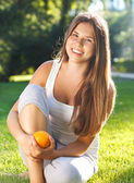 Beautiful young girl with open smile holding orange — Stock Photo