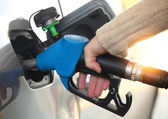 Mans hand refilling the car with a gas pump — Stock Photo