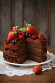 Piece of chocolate cake with icing and fresh berry — Stok fotoğraf