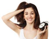 Surprised young brunette woman holding clock — Stock Photo