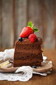 Kus čokoládový dort s polevou a čerstvé bobule — Stock fotografie
