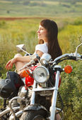 Young biker woman on the country road — Stock Photo