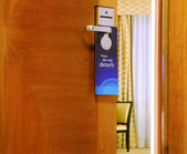 Please do not disturb sign hanging on open door — Stock Photo