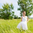 Smiling brunette little girl on meadow — Stockfoto