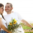 Happy young smiling couple with flowers — Stock Photo