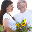 Happy young smiling couple with flowers — Stock Photo #19379451