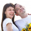 Happy young couple with flowers — Stock Photo #19379469