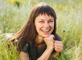 Smiling brunette woman on meadow — Stock Photo