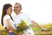 Happy young smiling couple with flowers — Stock fotografie