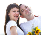 Happy young couple with flowers — Stock Photo