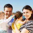 Happy young family with two children outdoors — Stock Photo #19997801
