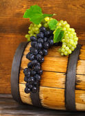 Still life with barrel decorated red and white grapes — Stock Photo