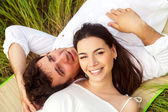 Happy young smiling couple on the summer meadow — Stock Photo