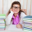 Little brunette smiling girl doing her homework — Stock Photo