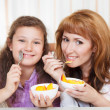 Stock Photo: Mother and daughter eating cereal and fruit