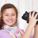 Little girl saving money in a piggybank — Stock Photo
