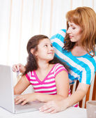Young woman with girl using laptop computer — Stock Photo