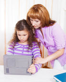 Young woman with girl using tablet computer — Stock Photo