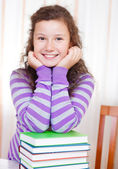 Little brunette smiling girl with books — Stock Photo