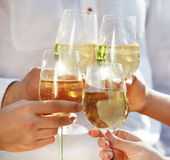Holding glasses of white wine making a toast — Foto Stock