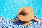 Woman in a hat enjoying a swimming pool — Stock Photo
