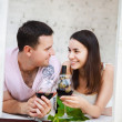 Stock Photo: Young happy couple enjoying glasses of red wine