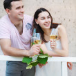 Young happy couple enjoying a glasses of white wine — Stock Photo