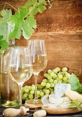 Still life with glasses of wine, bottle and chesse — Stock Photo
